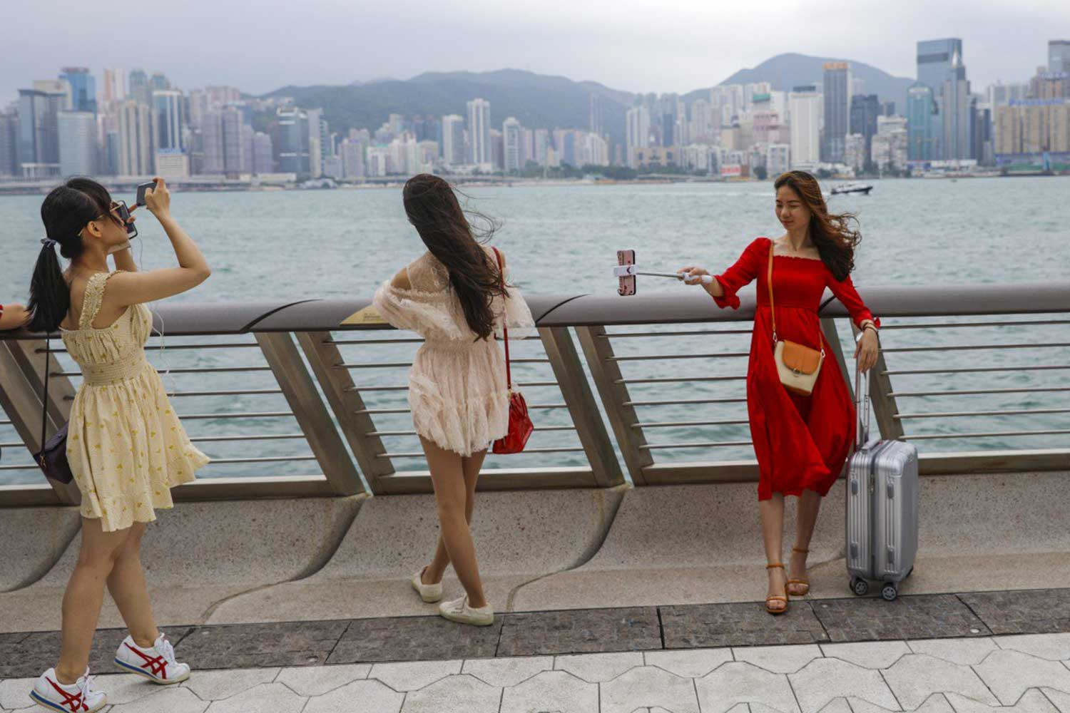 Tourists take pictures during a visit to the Avenue of Stars at Victoria Harbour in Tsim Sha Tsui. (South China Morning Post photo)