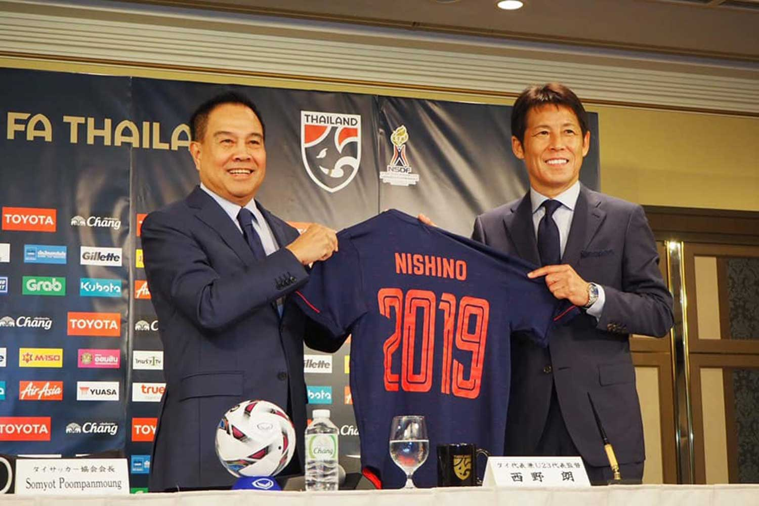 Football Association of Thailand president Pol Gen Somyot Poompunmuang presents a T-shirt bearing the name of the new national men's team coach after Akira Nishino signed his contract in Tokyo on Friday. (Football Association of Thailand photo)