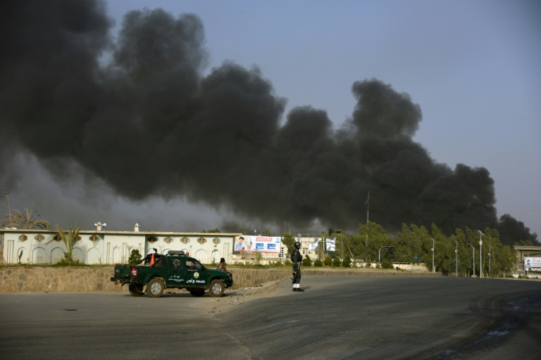 Afghan police arrive near a site of car bomb attack as smoke rises from the Police headquarters in Kandahar province on July 18, 2019. At least 11 people were killed and scores more wounded when the Taliban attacked a police headquarters in the southern city of Kandahar, officials and the insurgents say.