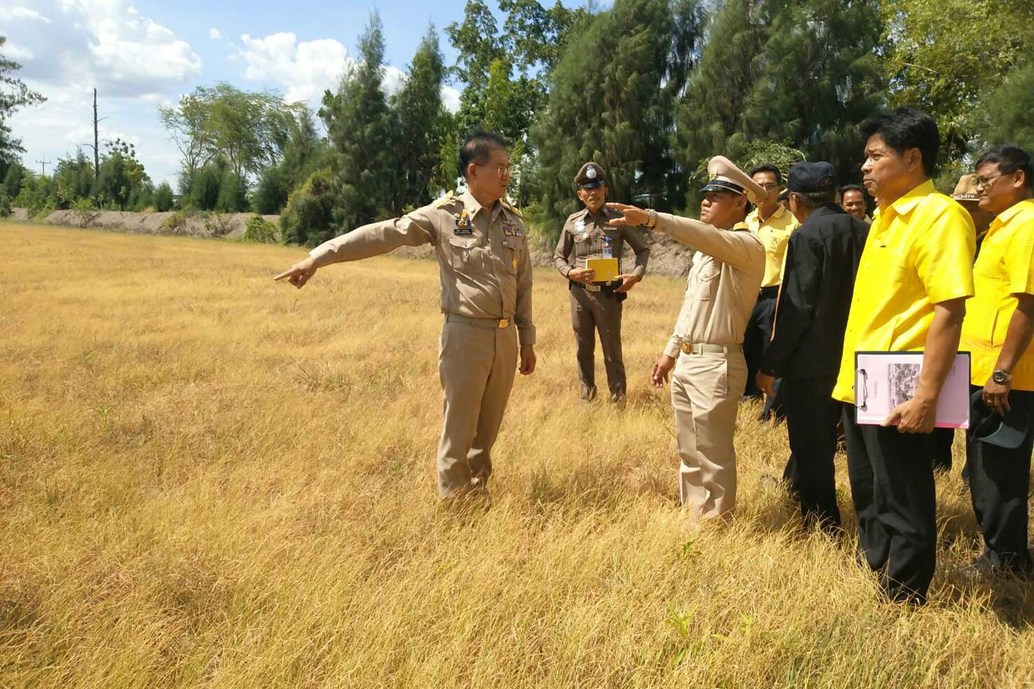 Nakhon Ratchasima Governor Wichian Chantharanothai, front, visits a parched paddy field in Phimai district on Saturday. (Photo by Prasit Tangprasert)