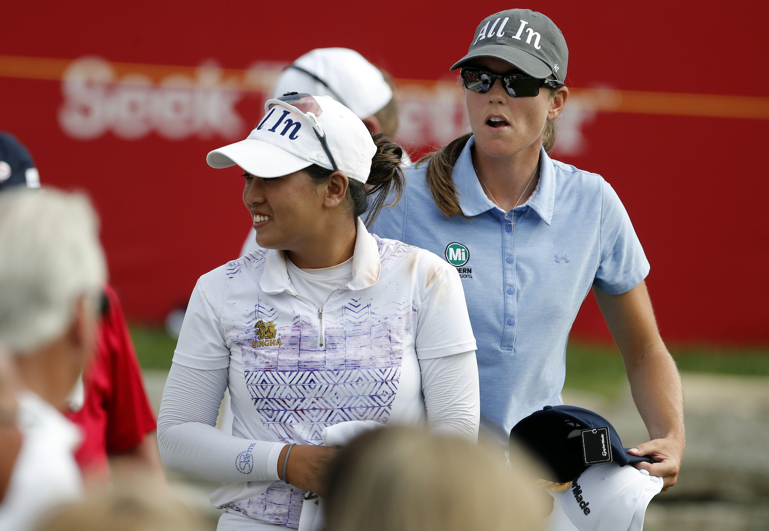 Jasmine Suwannapura (left) and teammate Cydney Clanton hand out caps to fans as they walk off the 18th tee during the third round of the Dow Great Lakes Bay Invitational golf tournament on Friday in Midland, Michigan. (AP Photo)
