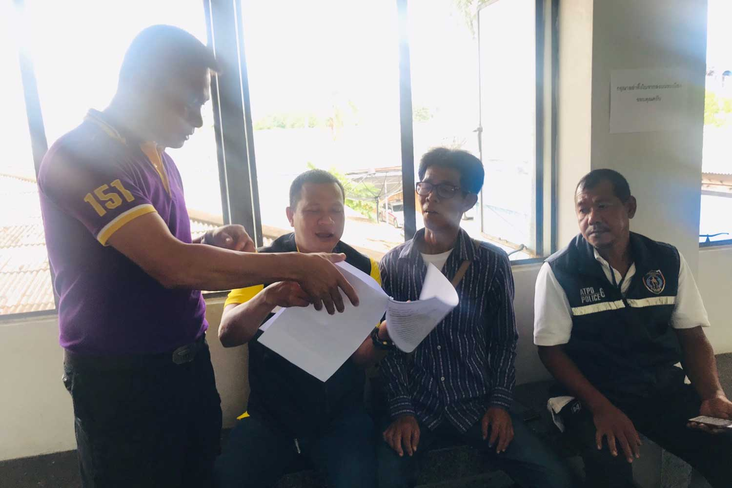 Investigators question Kosol Kliewklai (wearing glasses) after taking him into custody on a charge of raping his friend's 10-year-old daughter. (Supplied photo via Wassayos Ngamkham)