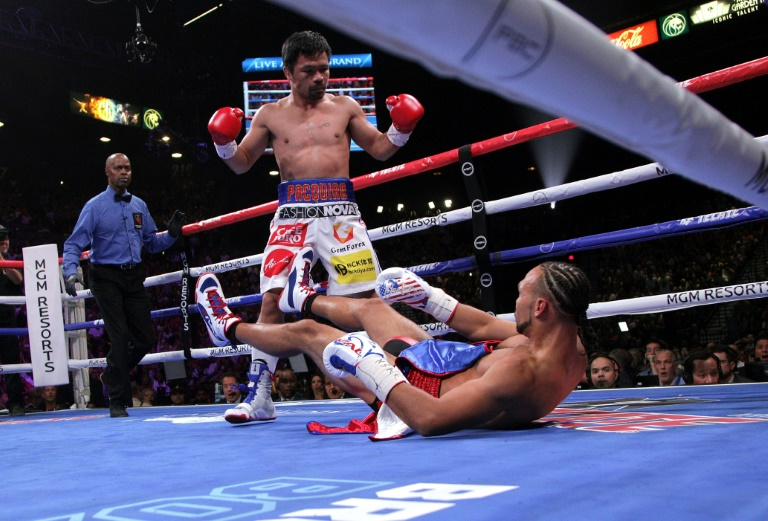 Manny Pacquiao sends Keith Thurman to the mat during the first round of their WBA super world welterweight title fight.