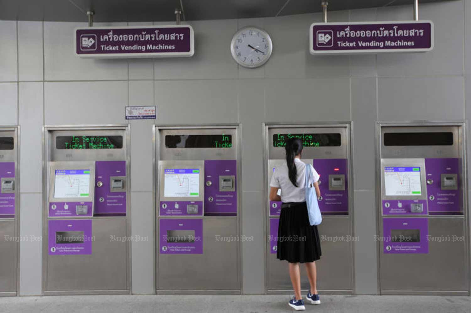 A commuter buys a ticket on the Purple Line electric railway in Bangkok. (File photo by Wichan Charoenkiatpakul)