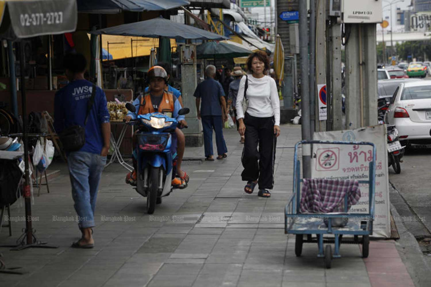 A motorcycle taxi driver travels along a footpath in Bangkok's Bung Kum district, weaving between pedestrians, on Nov 28 last year. (File photo)