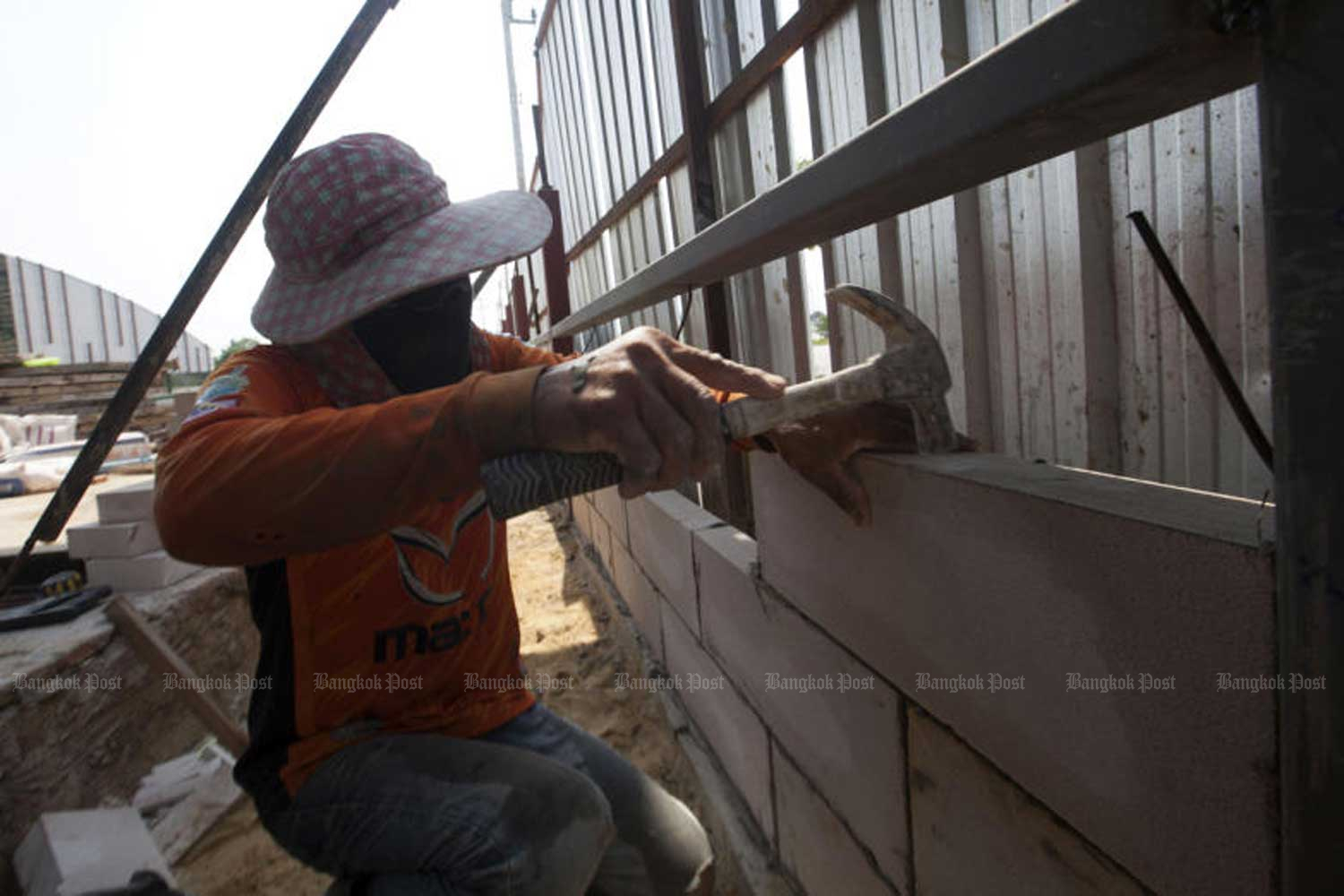 A labourer works at a construction site in Bangkok. The Board of Trade of Thailand said on Friday most employers opposed the government policy's to raise the minimum daily way to at least 400 baht, deeming it too costly. (File photo by Pawat Laopaisarntaksin)