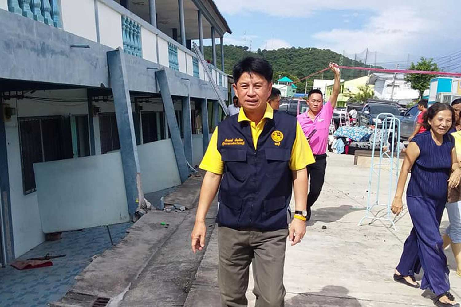 Chon Buri governor Pakkhathorn Thianchai leads officials to inspect a seaside building containing 16 rooms for rent in Muang district of Chon Buri after it subsided on Monday afternoon. (Photo taken from @ChonburiPr Facebook page)