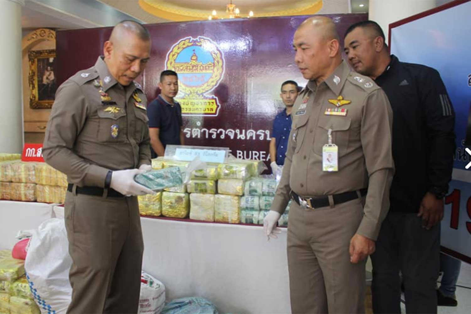 Pol Gen Chalermkiart Srivorakhan, deputy national police chief, (left), examines a package of seized illicit drugs during a news conference at the Metropolitan Police Bureau on Thursday. (Photo taken from @fm91trafficpro Facebook page)
