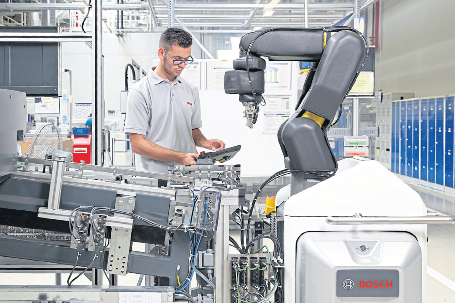 A worker is controlling Robert Bosch's APAS robot during a task.