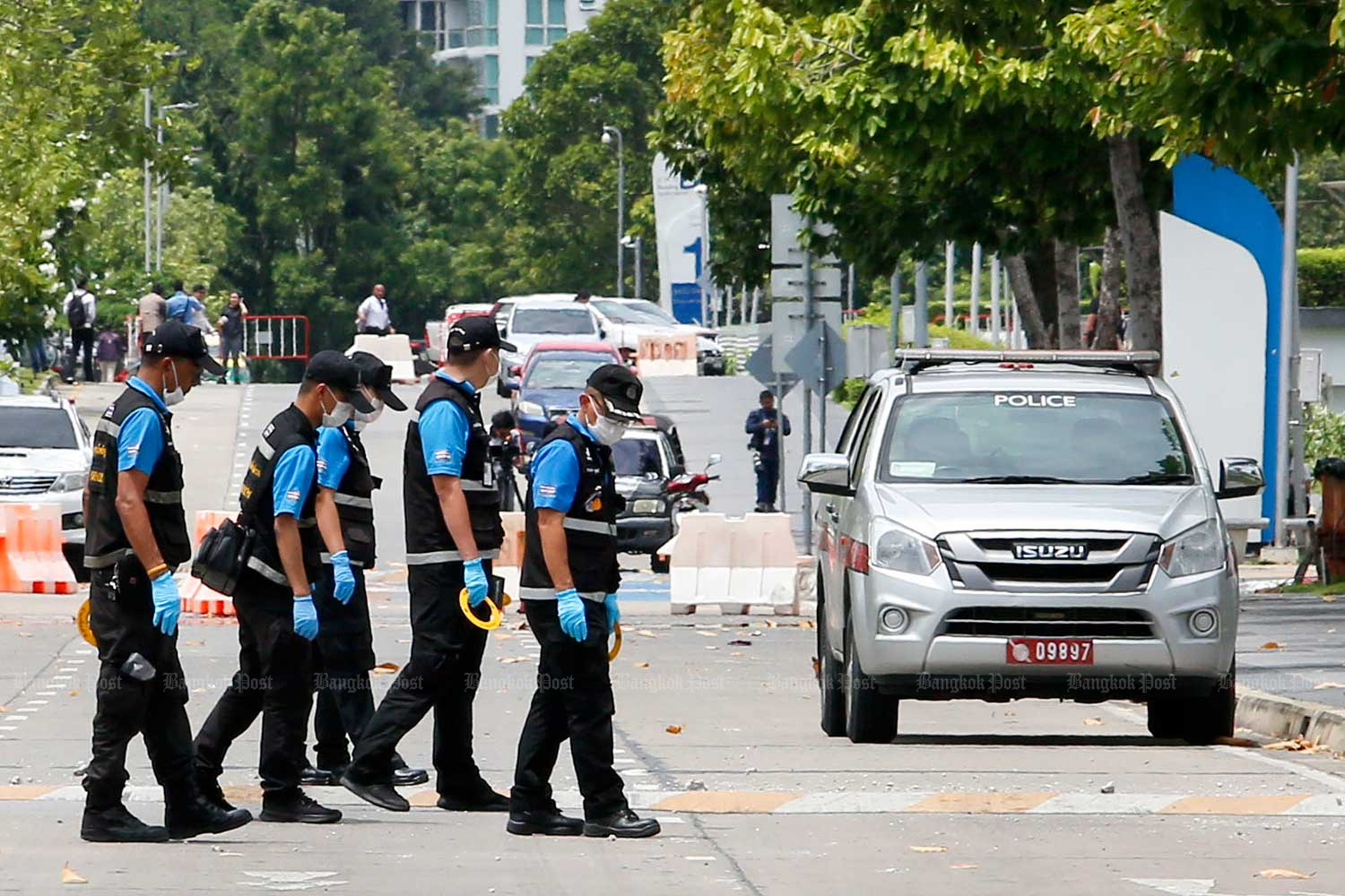 Bomb squad officers check the Government Complex on Chaeng Watthana Road after one of two bombs went off on Friday. (Photo by Pattarapong Chatpattarasill)