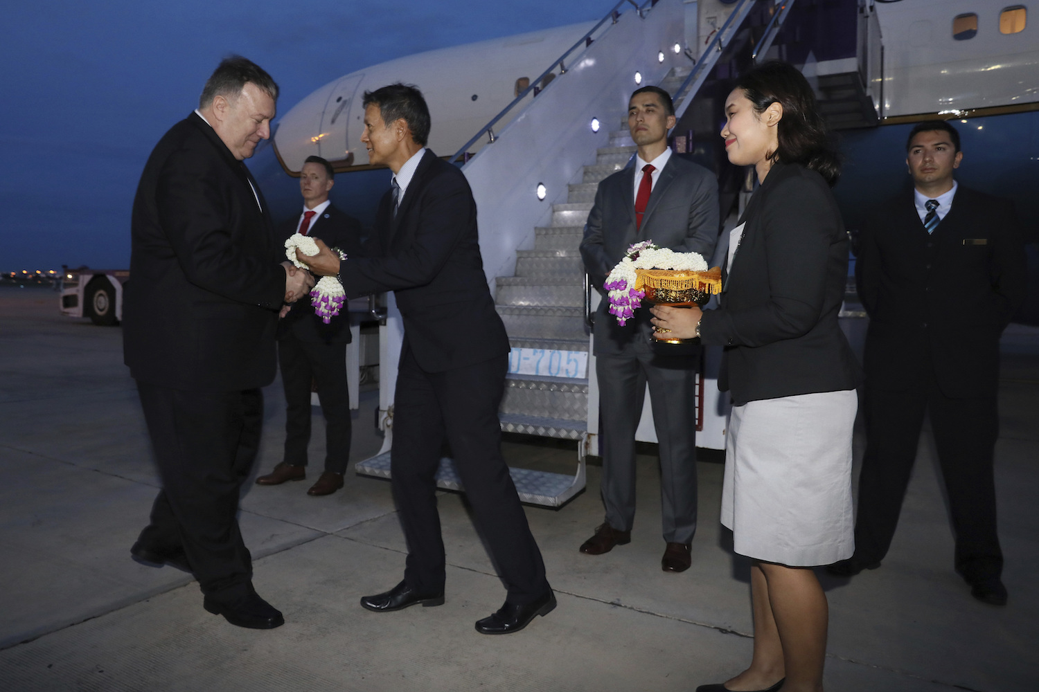 US Secretary of State Mike Pompeo is presented with flowers as he boards his plane to depart for Australia from Don Mueang airport on Saturday. (AP photo)