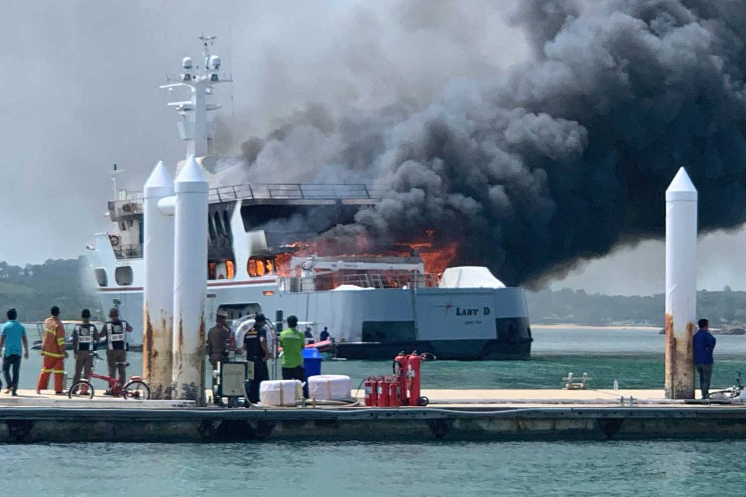 Smoke nd flames billow from the burning 240 million baht super yacht moored off a pier in Thalang district, Phuket, on Wednesday morning. No one was injured.  (Photo by Achadtaya Chuenriran)
