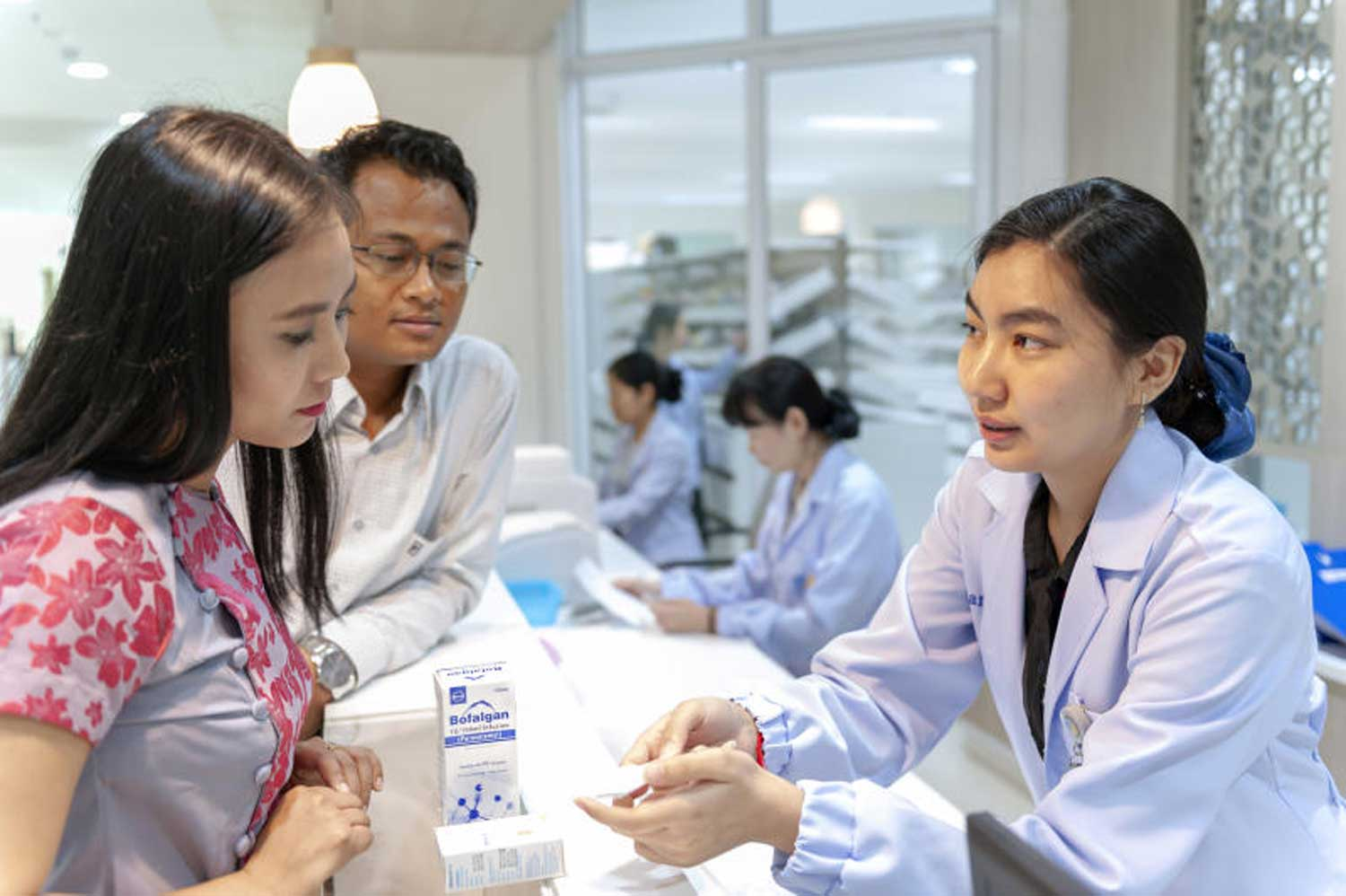 A pharmacist dispenses medicine to a patient at a private hospital. Medical supplies and service charges at private hospitals are now on the state price control list. (File photo)