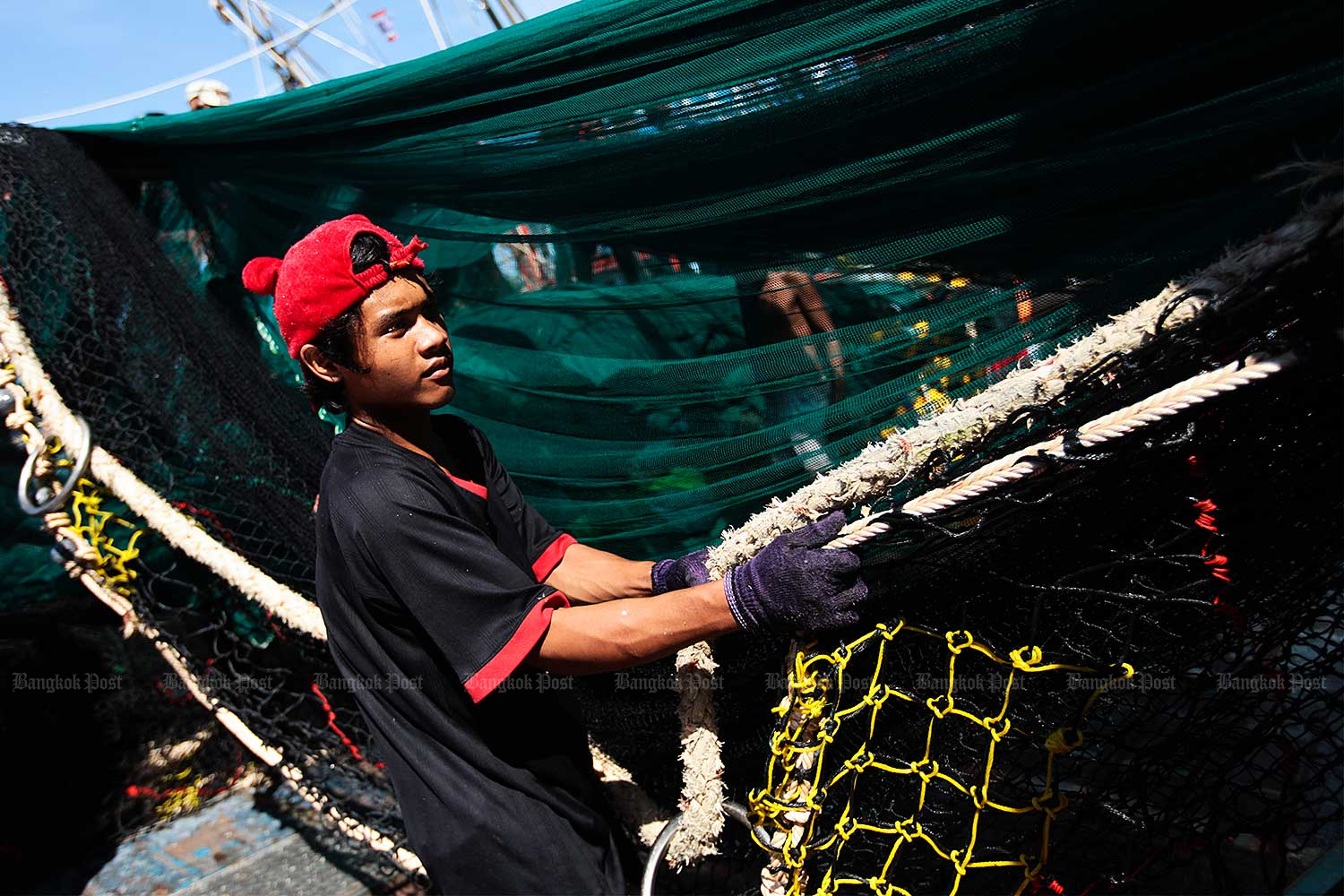 In this file photo, a young Myanmar worker pulls a fishing net while working at Ban Nam Khem wharf in the southern province of Phangnga. He is one of about 1 million migrant workers from neighbouring Myanmar who are now living and working in Thailand. (Photo by Patipat Janthong)