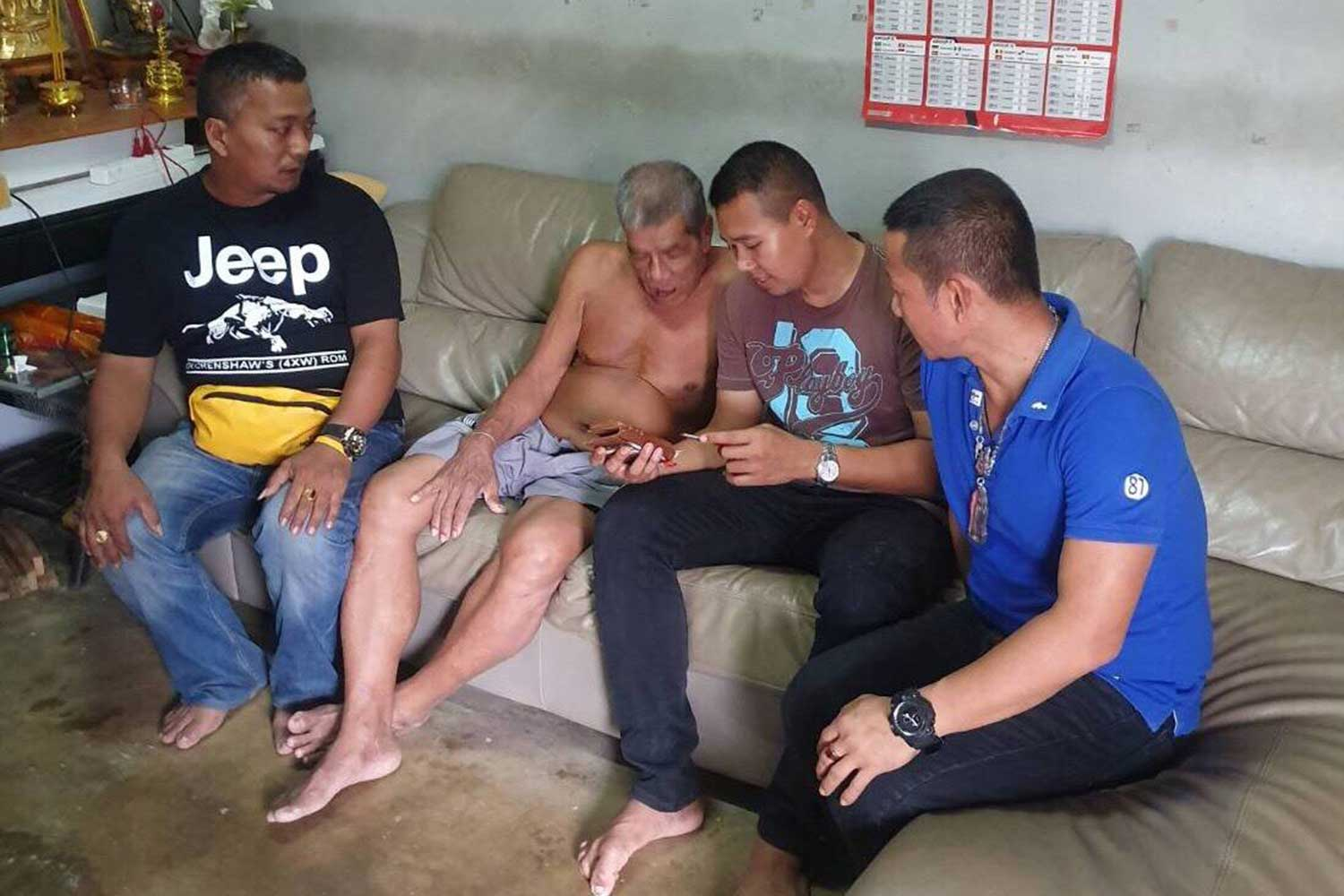Plainclothes officers question Honchao Sae Oun (second from left), at his house in Phangnga about an assault he was accused of committing in late 2004. (Crime Suppression Division photo)
