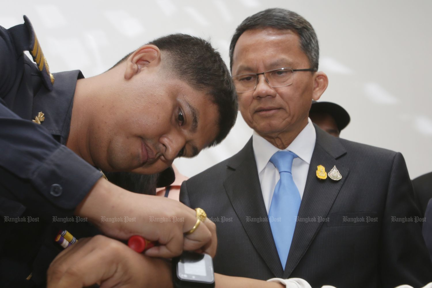 Justice Minister Somsak Thepsuthin watches as an official demonstrate the use of an electronic monitoring bracelet at the ministry on Friday following complaints the device can be removed and put back on. (Photo by Apichit Jinakul)