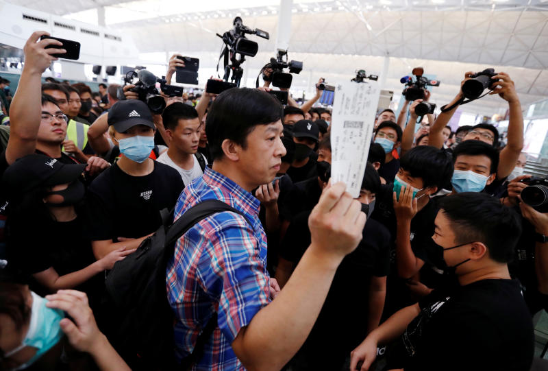 A passenger walks past anti-government protesters as he tries to enter the security gate during a demonstration at Hong Kong Airport, China on Tuesday. (Reuters photo)