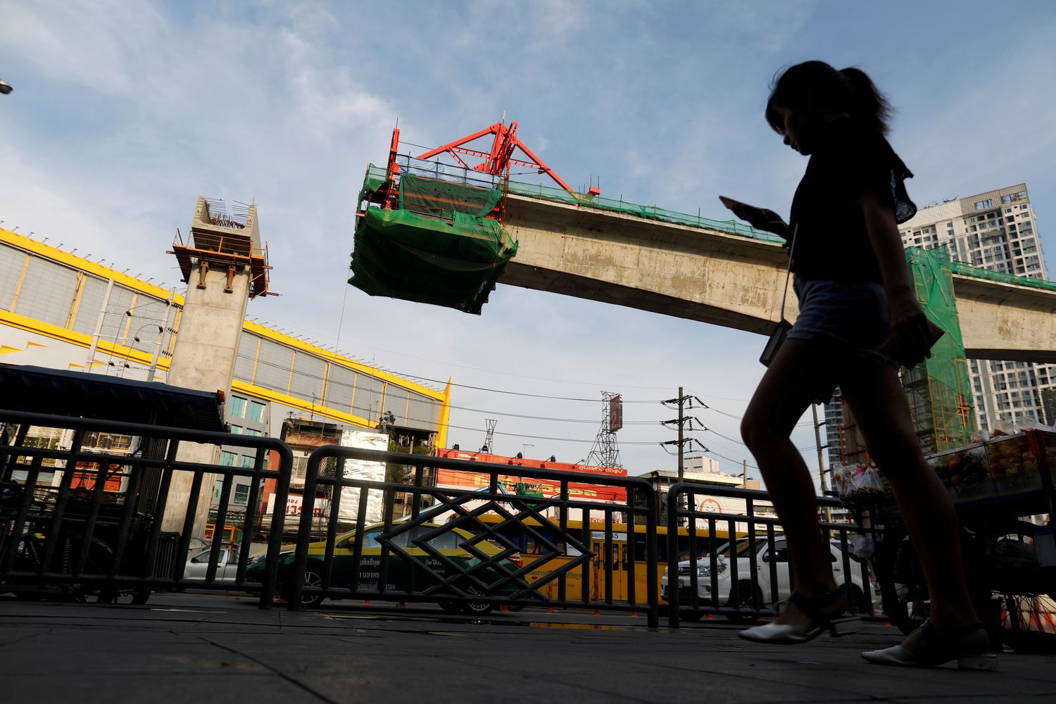 A girl walks past a skytrain construction site in Bangkok in May last year. (Reuters photo)
