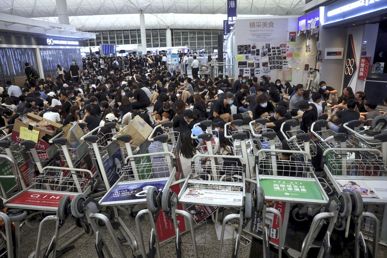 Protesters use luggage trolleys to block the walkway to the departure gates during a demonstration at the airport in Hong Kong on Tuesday.(AP photo)