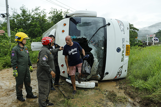 An Italian tourist exits the front of a bus after it overturned in Mae Tha district of Lampang province on Friday. (Photo by Assawin Wongnorkaew)