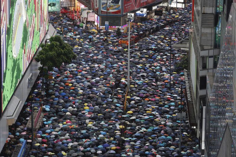 Demonstrators carry umbrellas as they march along a street in Hong Kong, on Sunday. (AP photo)