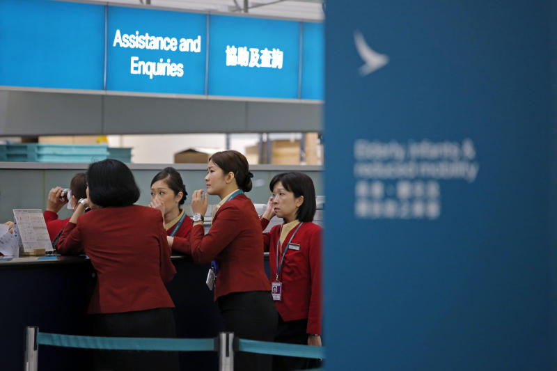 Staff members chat at the check-in counter ofCathayPacificAirways at Hong Kong airport on March 26, 2019. (AP photo)