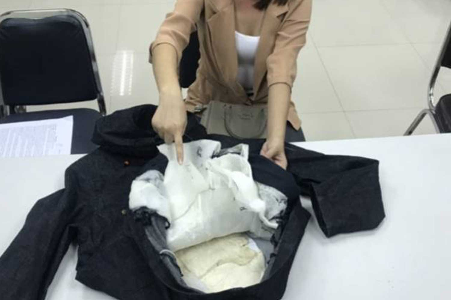 A Myanmar woman arrested by the police at a hotel room points at drugs during a media briefing. (Supplied photo)