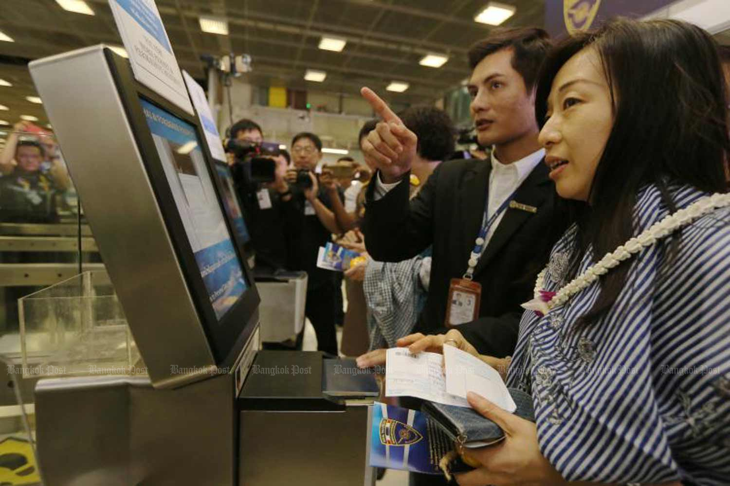 A Chinese tourist uses an e-immigration terminal at Suvarnabhumi airport. Cabinet has extended the visa-fee waiver for citizens of 18 countries until April, as part of an economic stimulus package. (File photo)