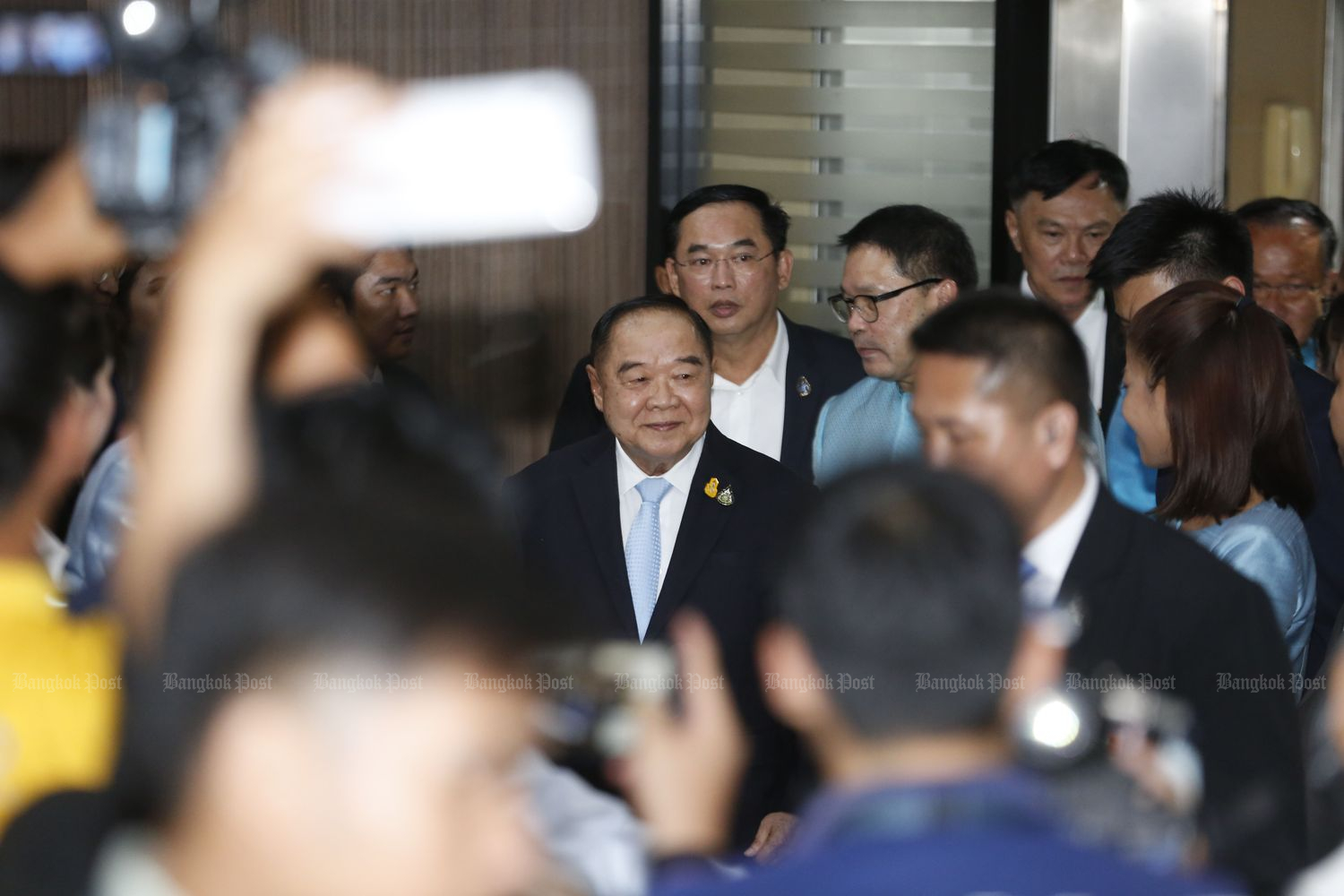 Gen Prawit Wongsuwon enters the Palang Pracharath Party's headquarters in Bangkok amid warm greetings by MPs and members on Tuesday. (Photo by Pornprom Sattrabhaya)