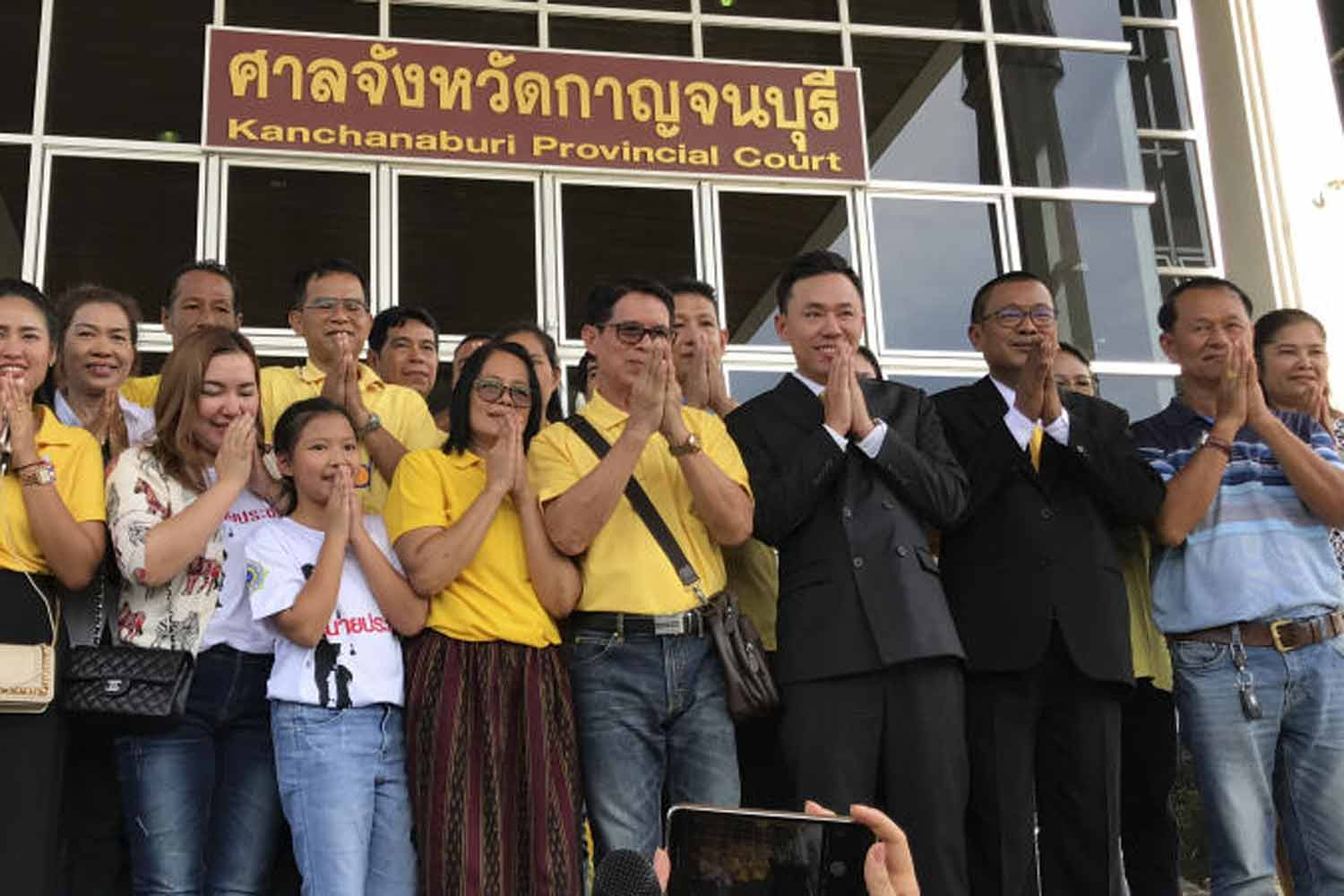 Retired Pol Lt Charoon Wimool, with shoulder bag, and supporters express their gratitude after the Kanchanaburi Court ruled in his favour on June 4, confirming his ownership of lottery tickets that won prizes totalling 30 million baht. (Photo by Piyarach Chongcharoen)