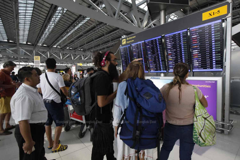 Travellers check flight information at Suvarnabhumi airport. (Bangkok Post photo)