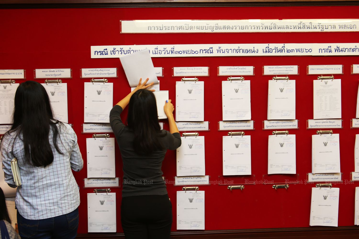 People check lists of assets and liabilities submitted by holders of political posotions and disclosed by the National Anti-Corruption Commission on Jan 19 last year. (Bangkok Post file photo)