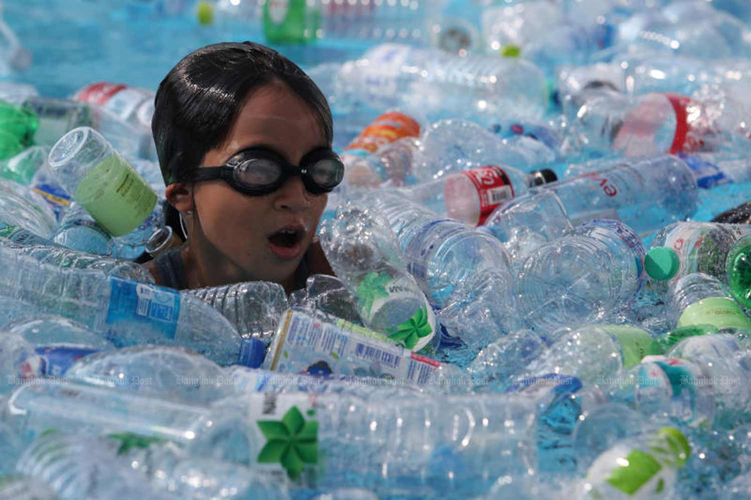 A school in Bangkok has students swim among plastic bottles to create awareness of plastic waste in oceans, on June 8 - the World Oceans Day. (Photo by Wichan Charoenkiatpakul)