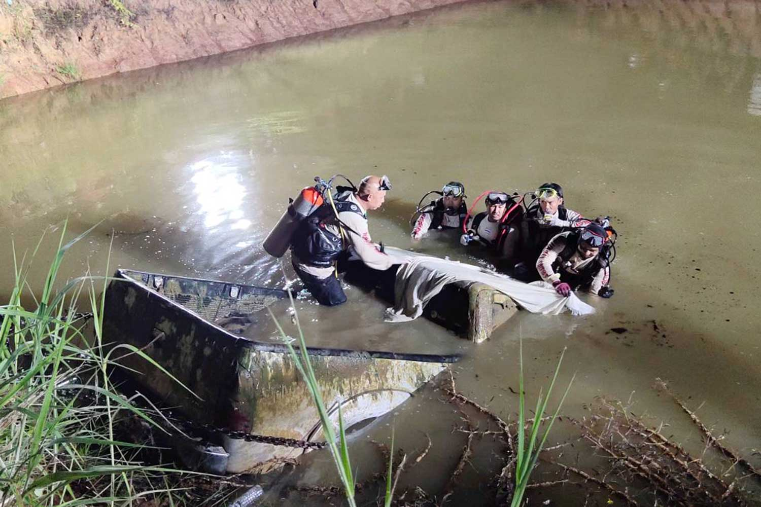 The pickup truck with the body of a man missing for eight months is hauled from a pond at a resort pond in Sikhiu district, Nakhon Ratchasima, late on Thursday night. (Photo by Prasit Tangprasert)