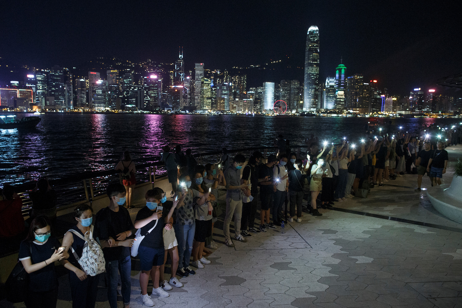 Protesters hold hands to form a human chain during a rally to call for political reforms at the Avenue of Stars in Hong Kong on Friday night. (Reuters Photo)