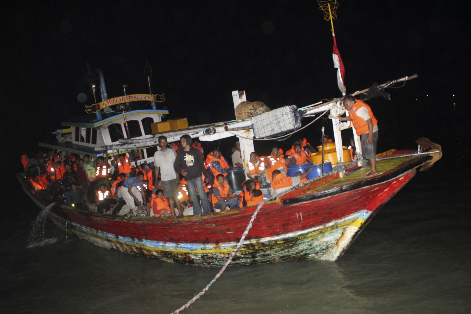 A fishing boat carrying survivors of a ferry that caught fire off Java island prepares to dock at a port in Sumenep, Indonesia, late Friday. (AP Photo)