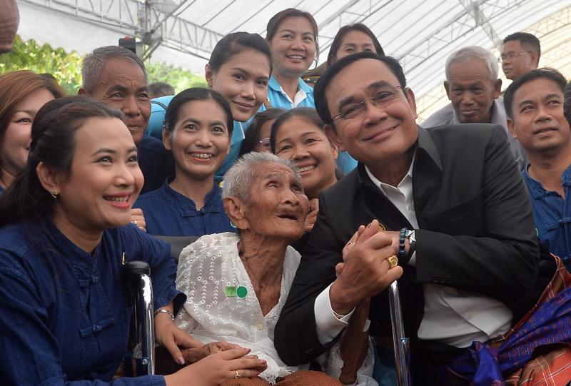 Prime Minister Prayut Chan-o-cha poses for a photo with residents in Surin on Monday during a visit to the province where Pheu Thai MPs for Surin welcomed him. (Government House photo)