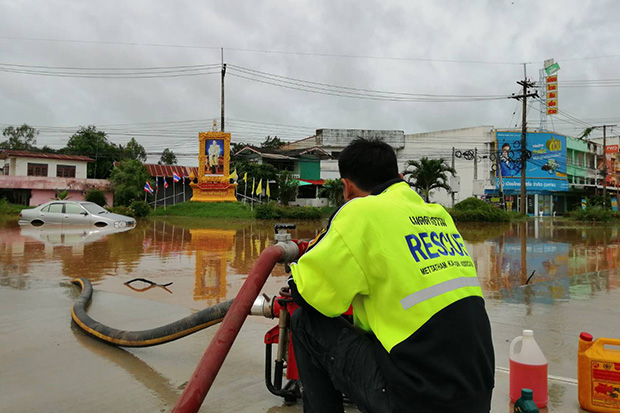 A rescue volunteer drains water from a flooded road in Kamalasai district in Kalasin on Monday after overnight rain pounded the northeastern province on Sunday night. (Photo by Yongyuth Phupuangphet)