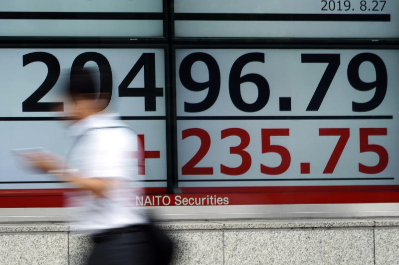 A man walks past an electronic stock board showing Japan's Nikkei 225 index at a securities firm in Tokyo on Tuesday. (AP photo)