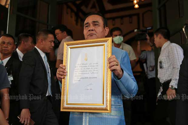 Prime Minister Prayut Chan-o-cha shows the message from His Majesty the King, after it was framed, at Government House on Tuesday. (Photo by Chanat Katanyu)