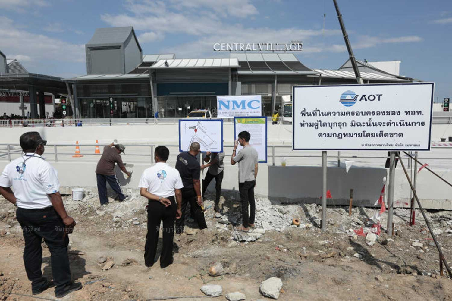 Officials from Airports of Thailand (AoT) put up signs in front of Central Village, a new luxury shopping complex due to open on Saturday. One sign warns it is AoT land  and trespassers will be prosecuted. (Photo by Patipang Janthong)