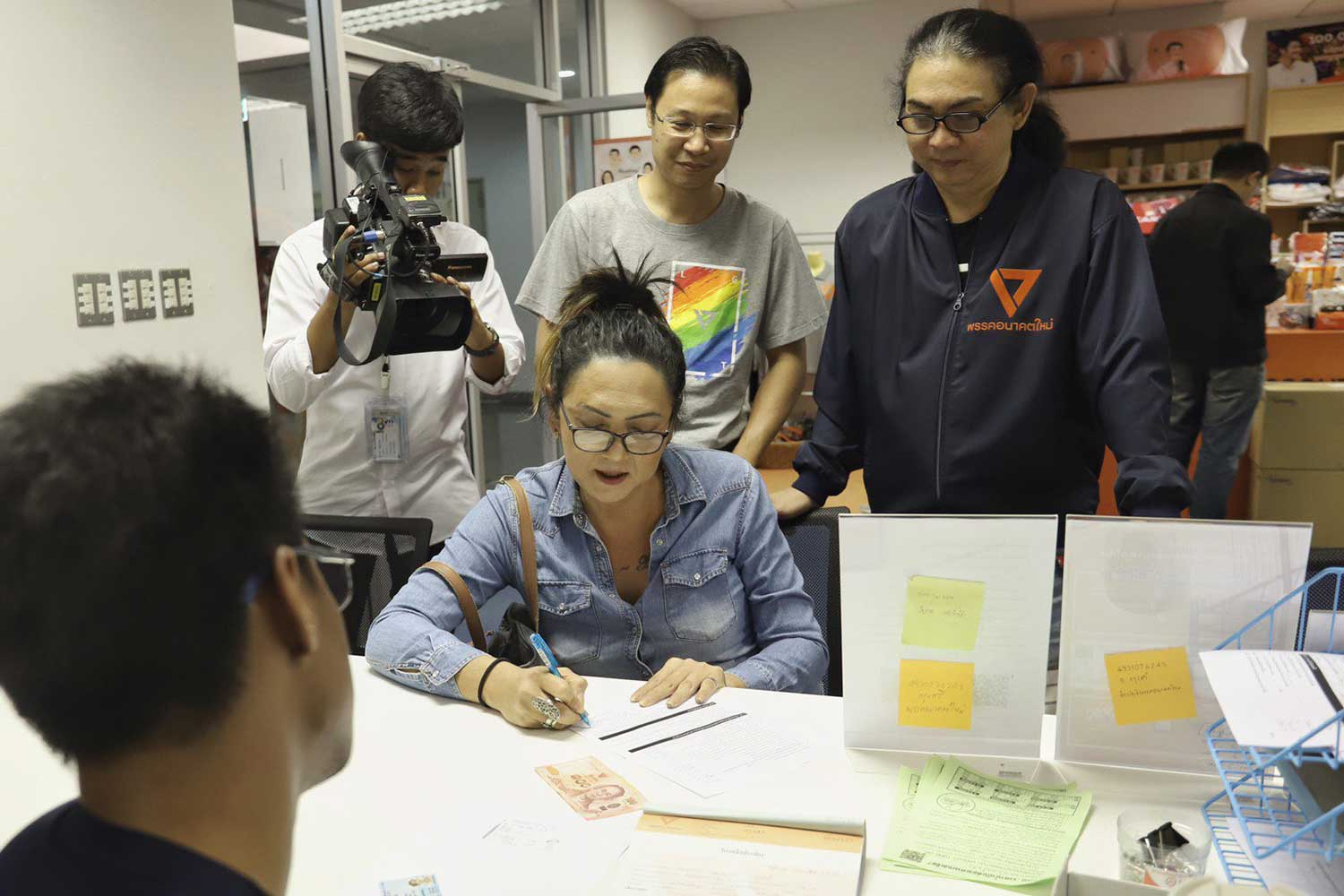 Pauline Ngampring fills out a membership application at the Future Forward Party office on Wednesday. (Photo from @FWPthailand Twitter account)