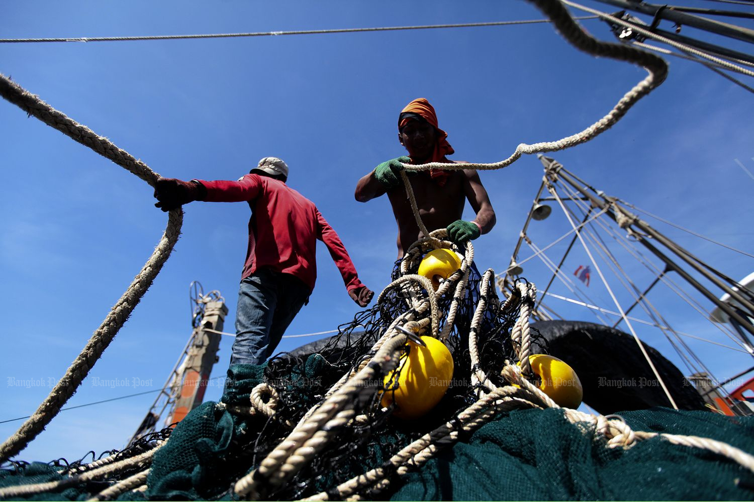Migrant labourers work on a fishing boat docked at a pier in Phangnga province in November 2014. (Bangkok Post file photo)