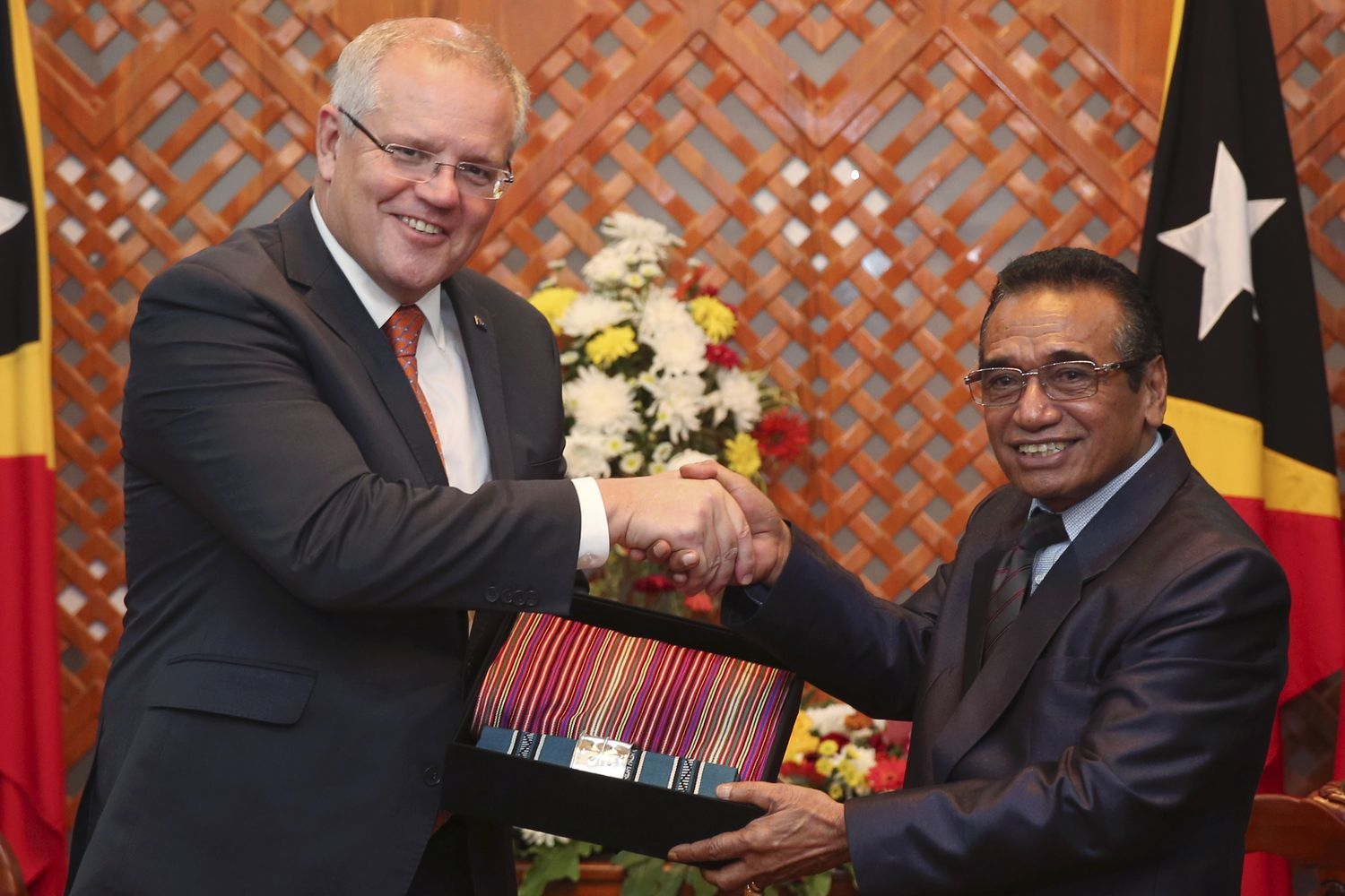 Australian Prime Minister Scott Morrison (left) receives a souvenir of traditional Timorese woven cloths called 'tais' from East Timorese President Francisco Guterres during their meeting in Dili, East Timor, on Friday. (AP photo)