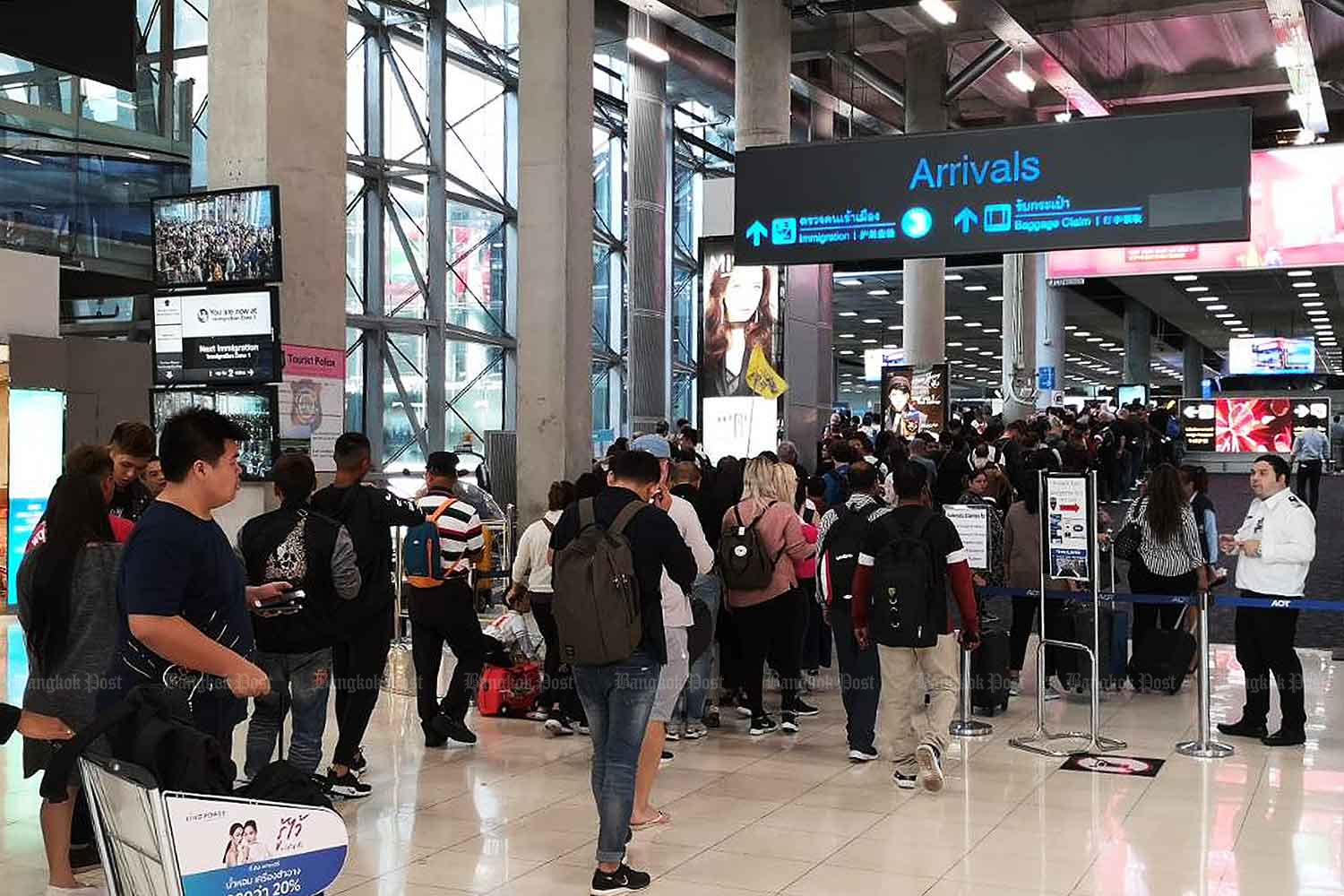 Tourists join the immigration queue upon arrival at Suvarnabhumi airport. The government says the enforcement of TM30 is mainly a national security measure. (Bangkok Post file photo)