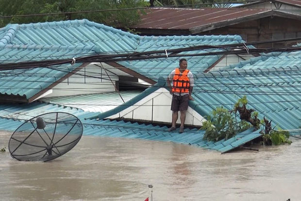 No way out: A man is seen stranded on Saturday on the roof of his home following flash flooding in the Saphan Khao community in tambon Nai Muang of Khon Kaen's Ban Phai district. (Photo by Chakkrapan Natanri)