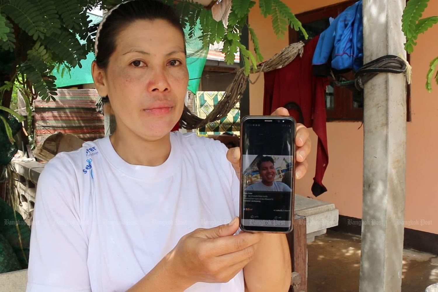 Silakorn Chanthopaeng on Sunday shows a picture of her son Sarawut, who died of electrocution as he was helping other people to escape floodwater in Ban Phan district in Khon Kaen. (Photo by Chakrapan Nathanri)