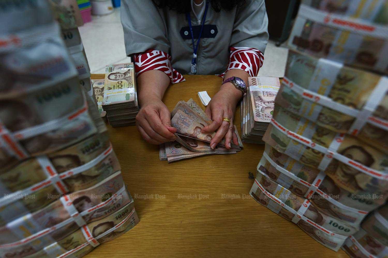 A bank employee counts 1,000-baht banknotes at Bangkok Bank's headquarters.(Photo by Somchai Poomlard)