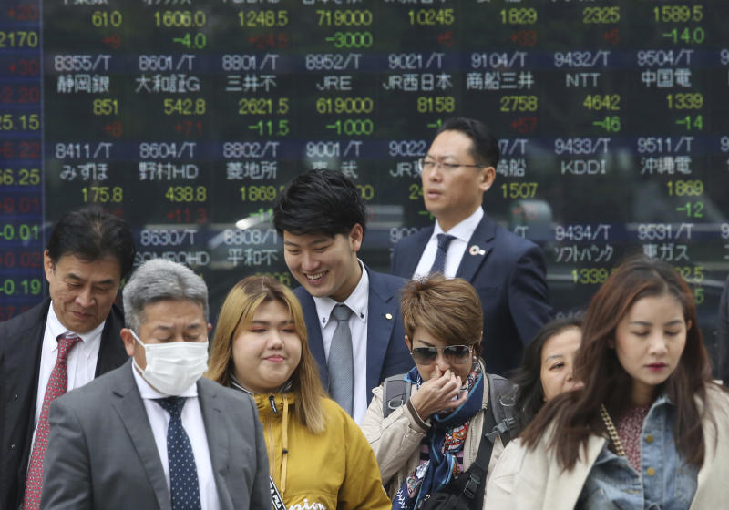 People stand in front of an electronic stock board of a securities firm in Tokyo, April 17, 2019. (AP file photo)