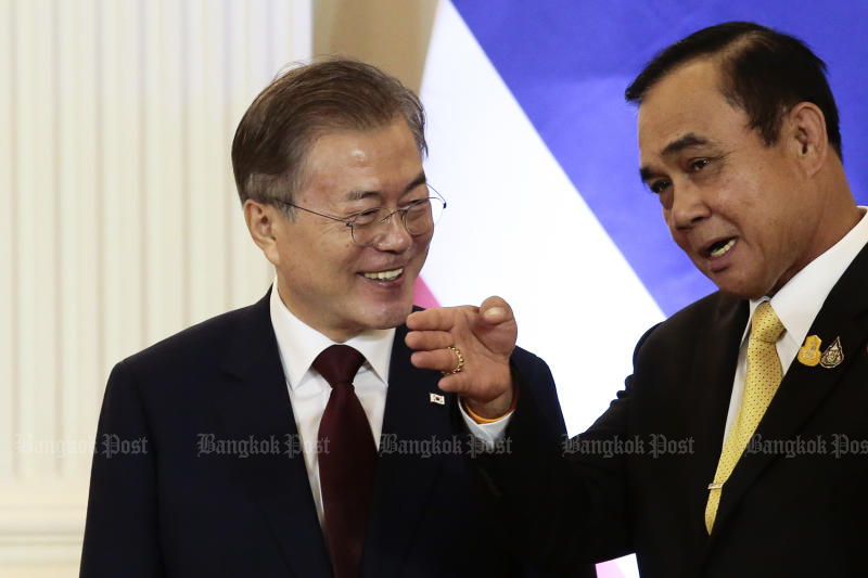 Prime Minister Prayut Chan-o-cha South Korean President Moon Jae-in share a light moment before a press conference at Government House on Monday. (Photo by Patipat Janthong)